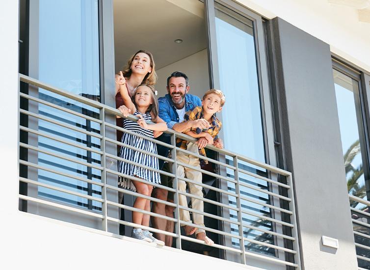 rodzina wyglądająca przez okno balkonowe